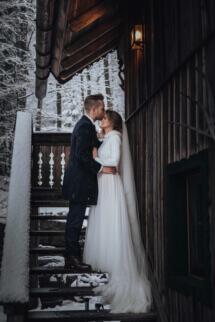 Romantische tief verschneite Winterhochzeit in den Bergen, Brautpaar beim Paarshooting auf einer romantischen Berghütte