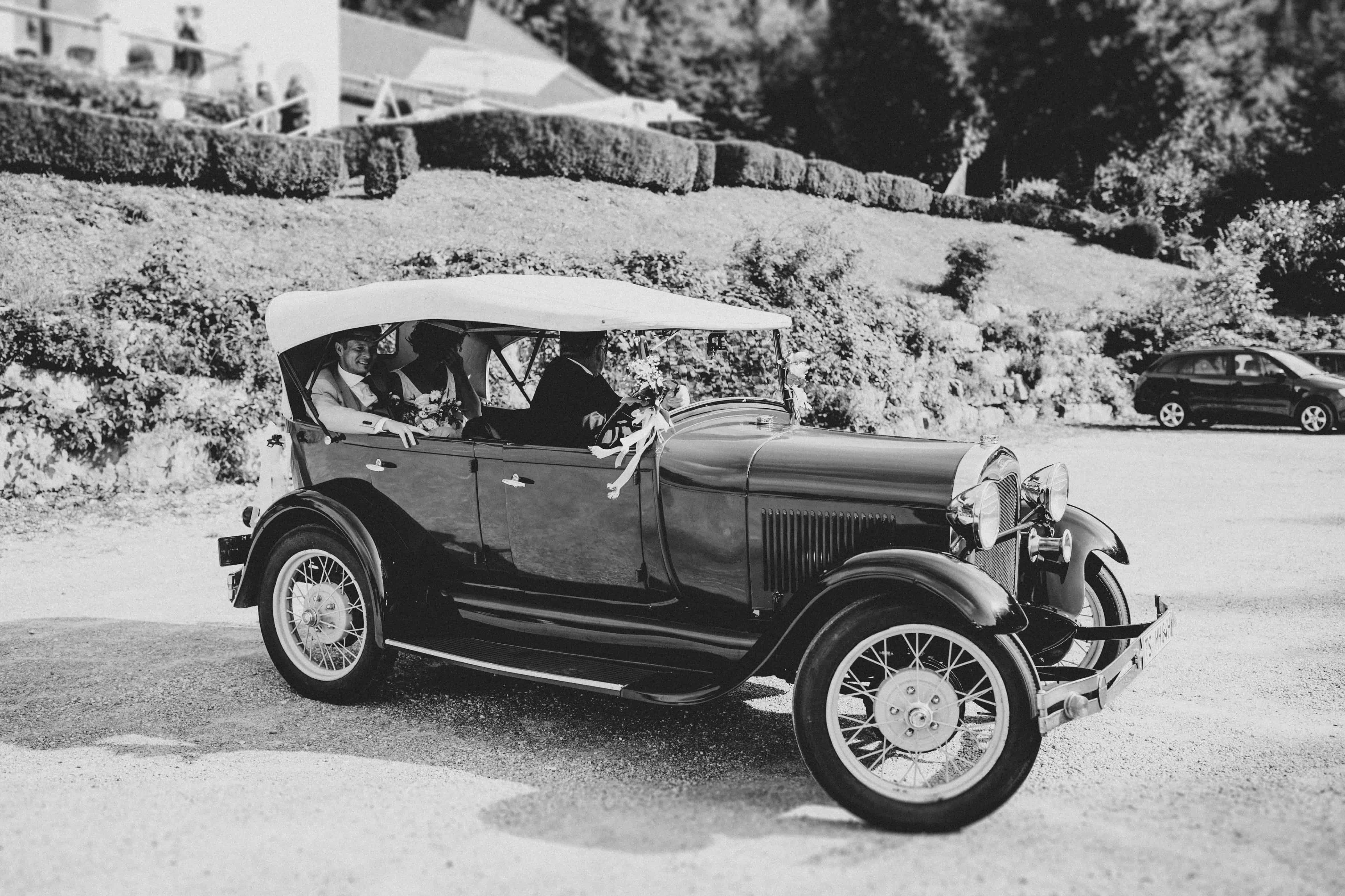 Oldtimer Brautauto mit frisch vermählten Brautpaar und Chauffeur beim Parken bei der Hochzeitslocation bei einer wunderschönen Sommerhochzeit in den Bergen mit Hochzeitsplanerin pure passion weddings by Anna Walch