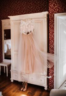 Was für ein wunderschönes Brautkleid für eine Winterhochzeit im Boho-Stil. Brautkleid vor der Anprobe in der Hochzeitssuite- perfektes Bild für die Hochzeitsfotografin