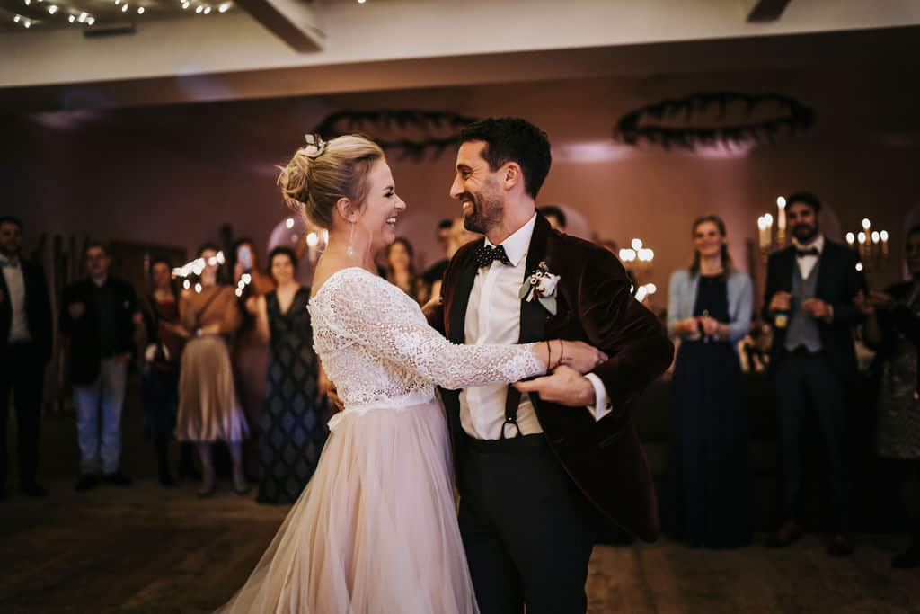 Ein überglückliches Brautpaar bei ihrem Hochzeitstag, die Hochzeitsgäste stehen im Kreis um das Brautpaar und haben Sprühkerzen in ihren Händen, was die romantische Stimmung perfekt macht. Hochzeitsplanerin pure passion weddings by Anna Walch