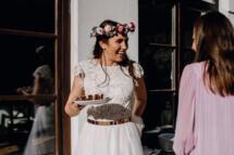 Glückliche Braut mit Blumenkranz bei einer Herbsthochzeit in Österreichs Bergen, die sich gerade ein Stück von der Hochzeitstorte geholt hat.